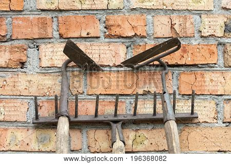 Still life of old rusty rake and hoe garden tools against the old weathered brick background making horizontal lines.