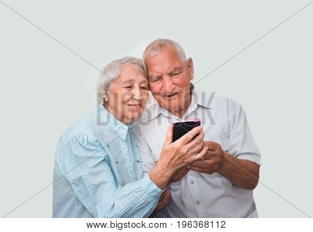 Senior couple at home using smartphones with happy emotions and sign OK