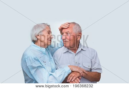 The elderly couple on the studio background. Concept of illness and good health