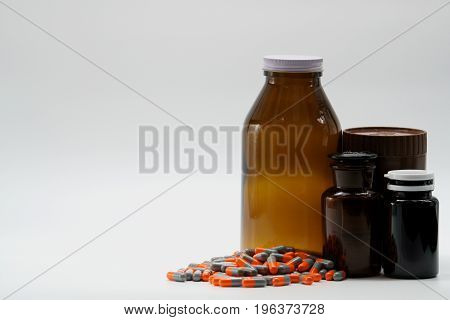 Capsule pills with amber bottles on white background