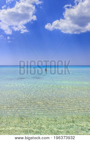 Sea colors of Italy.Summertime: relaxing at the nature. Summer seascape,Apulia coast: Marina di Pulsano beach (Taranto),  Lido Silvana bay. The most beautiful sandy beaches of Apulia: girl surrounded by turquoise crystalline water dominated by clouds,(Sal