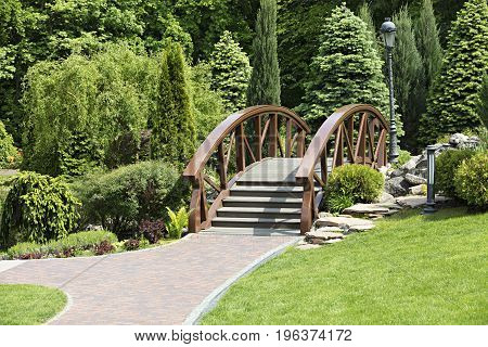 A small wooden bridge over the creek and paved sidewalk beautifully complements the general view of landscape design