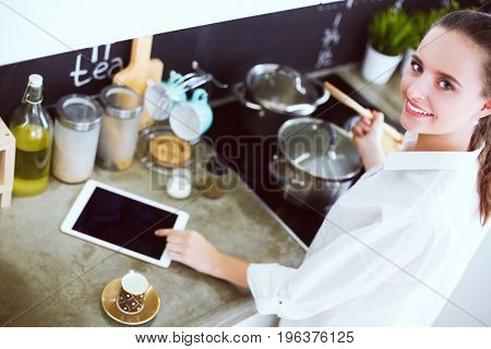 Young woman standing by the stove in the kitchen . Woman cooking in the kitchen.