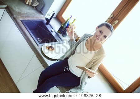 Beautiful young woman using a digital tablet in the kitchen.