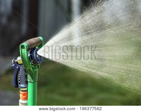 The sprinkler is attached to the spade shovel and sprays the water in the garden.