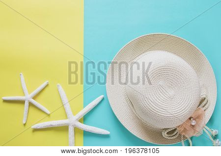 Summer Holiday Minimal Background Concept. Straw Hat, Starfishes On Yellow And Blue Background.