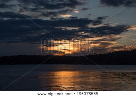 Sunset over the lake and forest in summer and around dark