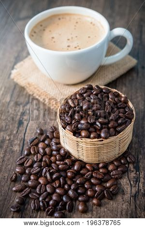 coffee beans in wooden basket and a white cup of cappuccino on sackcloth on wooden background