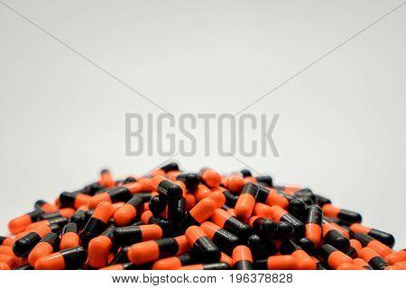 Orange black capsule pills on white background