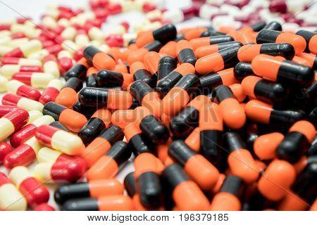 Orange black white red pale yellow capsule pills