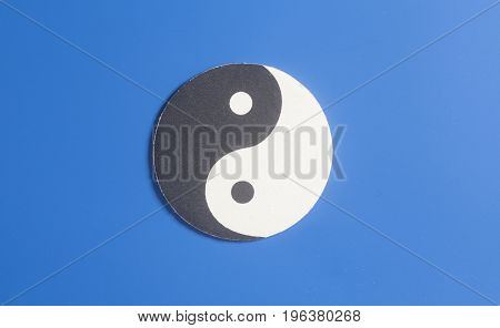 Yin-yang Symbol Made Of Paper On Blue Background.