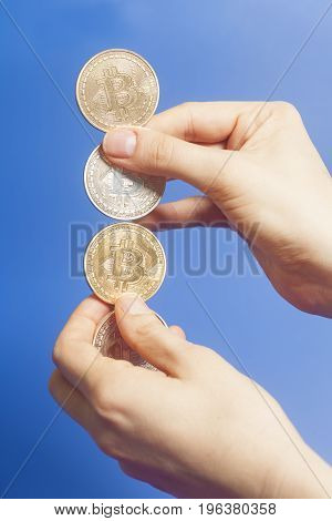 Four Virtual Coins Bitcoins In Hand On Blue Background