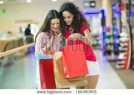 Two beautiful young women in a shopping center checking bags