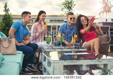 Friends having fun and drinking cocktails outdoor on a rooftop bar