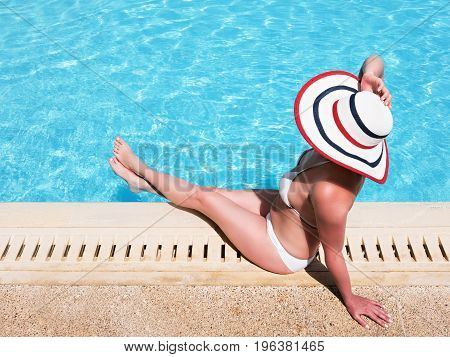 Beautiful woman sunbathing by the pool top view. Summer background. Woman sitting in swimming pool with sunhat.