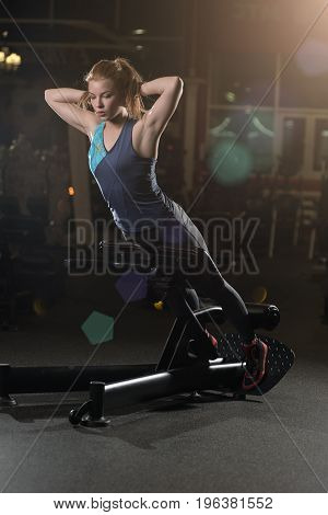 Woman doing strength exercises for abdominal muscles at indoor sport gym. Girl doing yoga stretches after running. Fitness model in dark sport club.