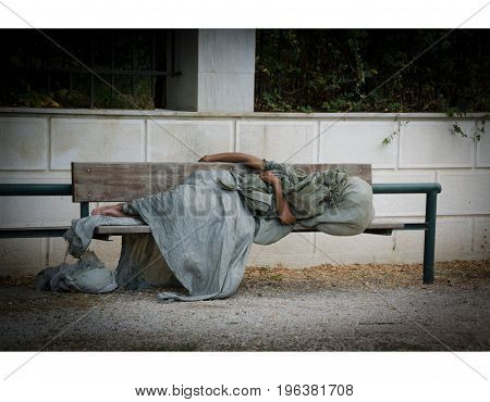 Homeless man is sleeping on a bench in the center of Athens