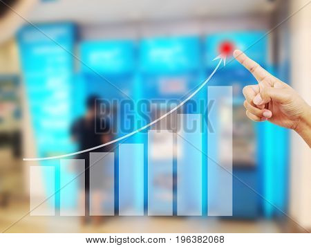Hand man to touch in peak of Business graph on abstract blurred background