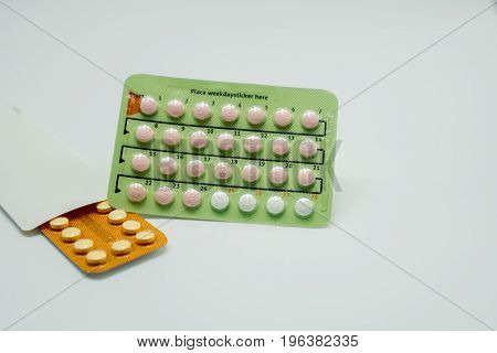 Two blister pack of contraceptive pills on white background