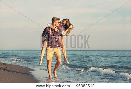 Happy couple in love on beach summer vacations. Joyful girl piggybacking on young boyfriend having fun.