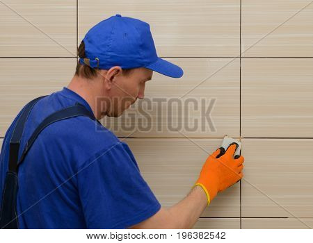 master-tiler blocks the seams between the tiles with beige cement grout