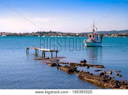 Destroyed pier and white small wooden fishing boat. View of Porto Heli town in the background. Greece