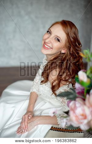 Portrait of beautiful red-haired girl sitting, smiling on big arm-chair. White dress, freckles, red-hair, background.