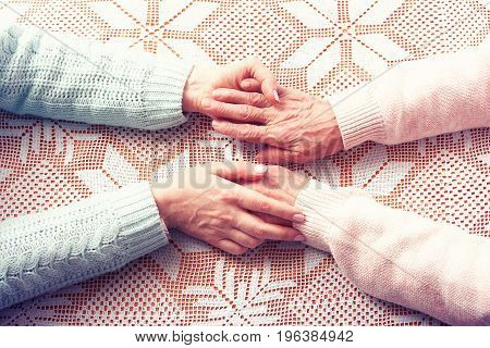 Care is at home of elderly. Senior woman with their caregiver at home. Concept of health care for elderly old people, disabled. Elderly woman holding hands closeup. Space for text white background.