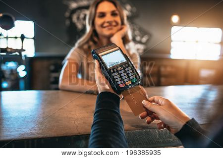 Cropped image of man paying using a credit card at bar with female behind the counter. Cashless payment at the bar.
