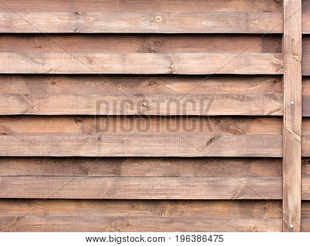 New horizontal wooden fence painted with protective composition