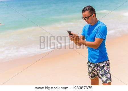 Man Use Phone On The Beach Typing Or Use Internet On Sunny Day
