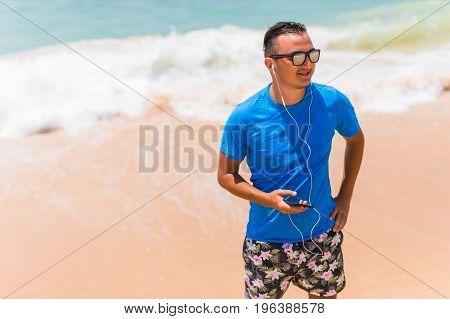 Happy Young Man Enjoying The Music On White Sandy Beach