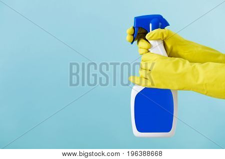Hand in a rubber yellow glove holds  spray bottle of liquid detergent on a blue background. cleaning