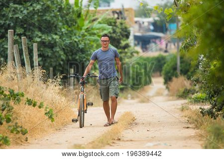 Time For A Cycle Handsome Young Smiling Man Walking Along A Road With His Bicycle