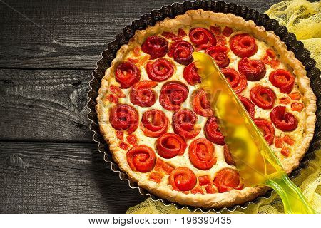 Delicious homemade pie with cheese cottage cheese pepper rolled up in roll in form of flower. Large cake in baking dish and knife on yellow gauze napkin on dark wooden table