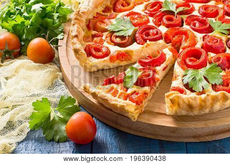 Delicious homemade pie with cheese cottage cheese pepper rolled up in roll in form of flower. Large cake on wooden round plate slice on scapula cherry tomatoes parsley on yellow gauze napkin