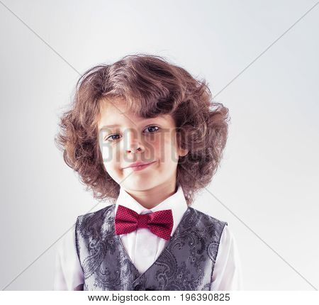 Curly cute boy in waistcoat and bow tie looking at the camera. Close-up. White background.