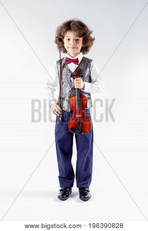 Cute curly violinist in waistcoat posing before the show. Full height. Gray background.