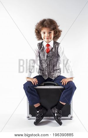 Cute curly little boy sitting on the black briefcase and looking forward. Gray background.