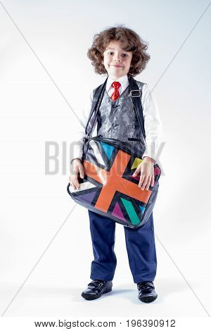Funny curly-haired boy in waistcoat holding a bag over his shoulder. Gray background.