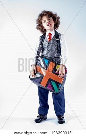 Funny curly-haired boy in waistcoat holding a bag over his shoulder his head bowed. Gray background.