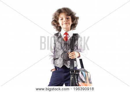 Funny curly boy stands in a waistcoat with a bag over his shoulder. White background.