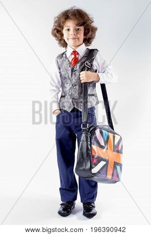 Cute curly boy stands with a bag over his shoulder. Full height. Gray background.