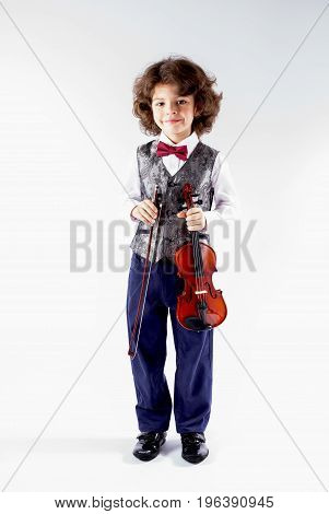 Cute curly violinist in waistcoat holding a violin and looking at the camera. Full height. Gray background.
