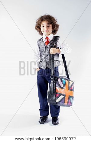 Funny curly-haired boy in waistcoat goes to school with a bag over his shoulder. Gray background.