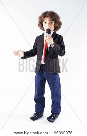 Young Handsome Businessman With A Microphone Stares Into The Camera. Full Length. Gray Background.