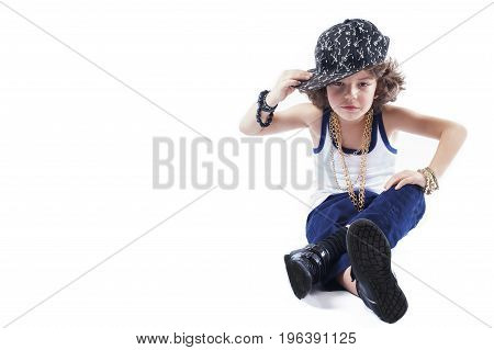 Cute Curly Rapper In A Baseball Cap Sitting On The Floor And Looking Into The Camera. White Backgrou