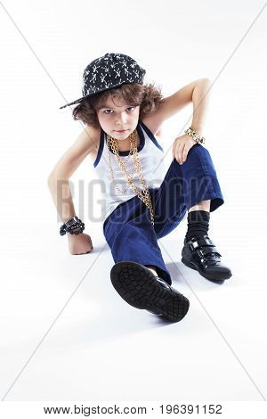 Little Curly Rapper In A Baseball Cap Sitting On The Floor And Looking Into The Camera. White Backgr