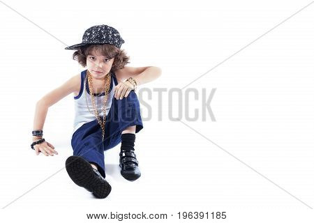 Little Curly Rapper Sitting On The Floor And Looking Into The Camera. White Background.