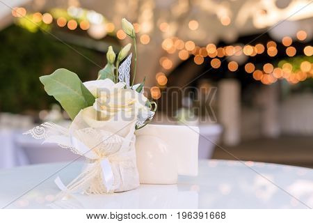 Flowers on the table in outdoor restaurant. Interior of a summer terrace of cafe. Table setting for wedding reception or an event. Copy space for text